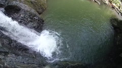 A young man cliff jumping into a river next to a waterfall. Stock Footage