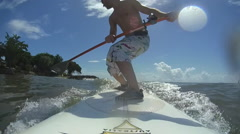 A young man standup paddle boarding off the island of Tobago. Stock Footage