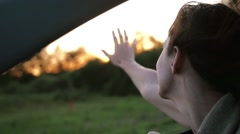 Pretty woman in a car enjoying the wind, hand playing in the air. Sun sets in Stock Footage
