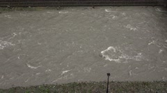 Gray opaque river water quickly flow between stony banks, muddy flow from dirty Stock Footage
