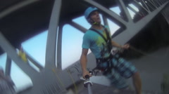 A young man rope swinging from a bridge. Stock Footage