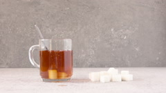 Sugar cube falling in glass tea cup in slow motion. Stock Footage