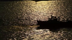 Motor boat dark silhouette, move backwards on glossy water ripples Stock Footage