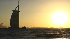 Sunset beach view, Burj Al Arab dark silhouette against bright low sunlight Stock Footage