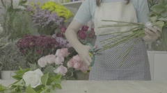 Dolly shot of florist woman trimming stems of white flowers, ungraded tone Stock Footage
