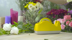 Florist woman binding beautiful flowers together with scotch tape Stock Footage