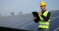 Electricity Engineer Man Holding Clip Board Taking Notes Looking Solar Panels Stock Footage
