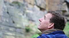 A portrait of a young man standing in preparation to go rock climbing bouldering Stock Footage