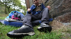 A young man preparing to go rock climbing bouldering. Stock Footage
