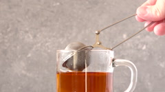 Making tea with teastrainer in a glass teacup. Stock Footage