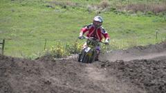 A young man riding a motocross dirt bike through a sprinkler. Stock Footage