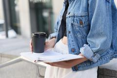 Paper cup and journal in student hands Stock Photos