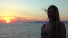Blonde model smiling into camera ocean sunset silhouette mykonos greece Stock Footage