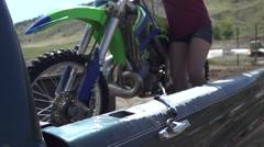 A teenage girl preparing to ride motocross dirt motorcycle. Stock Footage