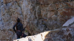 A young woman belays while rock climbing. Stock Footage