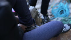 A young woman putting on climbing shoes before going rock climbing. Stock Footage