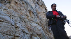 A young man preparing equipment to go rock climbing. Stock Footage