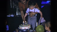 1951: mother helping a two year old boy blowing out candles at birthday party Stock Footage