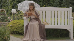 Girl with a white umbrella on the bench Stock Footage