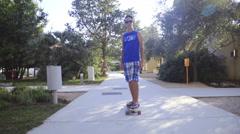 Teenager skateboarding through settlement on sunny day 4K Stock Footage