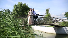 The bride and groom are standing on the bridge Stock Footage