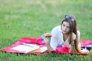 Feminine working lying in glasses in the park and food snack Stock Photos
