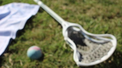 Lacrosse stick and ball on a grass field. Arkistovideo
