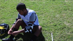 Lacrosse player putting on lacrosse gear and uniform. Stock Footage