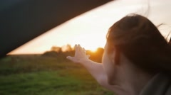 Happiness - young woman in a car, hand playing in the air. Beautiful sunset in Stock Footage