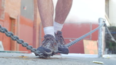 Man working out in the city balances on chain rope. Stock Footage
