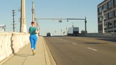 A young woman running in an urban environment. Arkistovideo