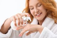 Joyful lady squeezing moisturizer on hand Stock Photos