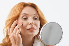 Senior red-haired lady having facial treatment Kuvituskuvat