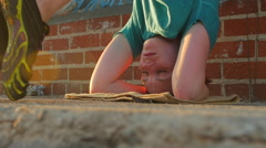 A young woman doing a headstand on the streets on an urban environment. Stock Footage
