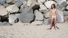 A young woman surfer standing in front of a rocky breakwater on the beach. Stock Footage