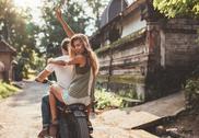 Couple enjoying motorcycle ride on village road Stock Photos