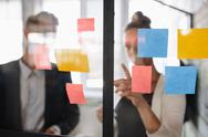 Business woman pointing at sticky note to male colleague Stock Photos
