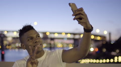 Tourist Holds Up Peace Sign For Selfie With Beautiful Lights In Background Stock Footage
