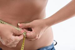 Fit lady taking measurements of her body Stock Photos