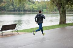 Athletic man running in a rainy day. Stock Photos
