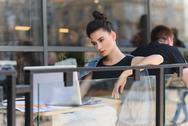 Female freelancer resting outside of a cafe Stock Photos