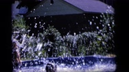 1964: a little girl splashes into an above ground pool in a backyard. CAMDEN  Stock Footage