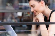 Female blogger looking into a screen of her computer Stock Photos