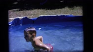 1964: two small boys swimming, diving and playing in a small pool  Stock Footage