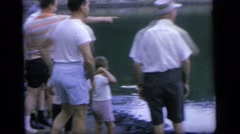 1964: people are standing on the shore of a lake with floating bags CAMDEN NEW Stock Footage