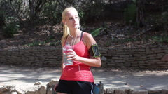 A young woman runner taking a break from her run to drink water. Stock Footage