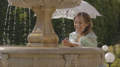 Girl with a white umbrella at the fountain Stock Footage