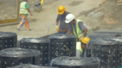 Rolls if bitumen close up, workers at building construction blurred by Sheyno. Stock Footage