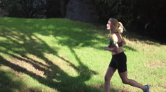 A young woman runner running in a residential neighborhood. Stock Footage
