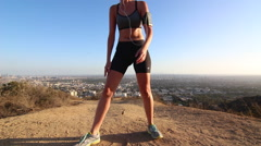 A young woman runner takes a break from running to catch her breath and admire t Stock Footage